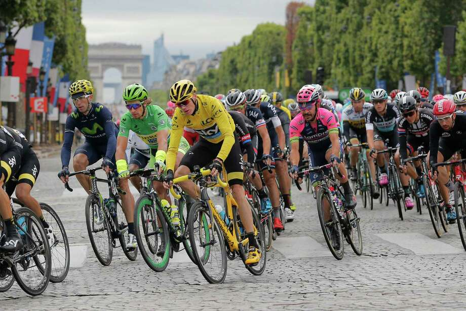 The pack with Britain's Chris Froome, wearing the overall leader's yellow jersey, and Peter Sagan of Slovakia, wearing the best sprinter's green jersey, ride down the Champs Elysees avenue during the twenty-first and last stage of the Tour de France cycling race over 109.5 kilometers (68 miles) with start in Sevres and finish in Paris, France, Sunday, July 26, 2015. (AP Photo/Christophe Ena) ORG XMIT: PDJ118 Photo: Christophe Ena / AP
