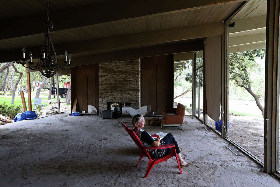 Alice Wightman, 66, looks towards the Blanco River while sitting in the living room of her flood ravaged home in Wimberley, Texas, Sunday, July 26, 2015. The area was hit with a historical flood on Memorial Day that left 1,200 houses and properties damages including 209 destroyed in Hays County. Twelve people died and two children are missing in the county. Wightman move into the home, located in the Wagon Wheel II subdivision off Flight Acres Road, in 2007 to help out her father, who bought it in 2005. The home, designed by architect George L. Walling, was built in the mid-1960Õs in a Frank Lloyd Wright style. She is hoping for a historical designation from the Texas Historical Commission, which would allow the house to be restored to its former glory. Photo: JERRY LARA, Staff / San Antonio Express-News / © 2015 San Antonio Express-News