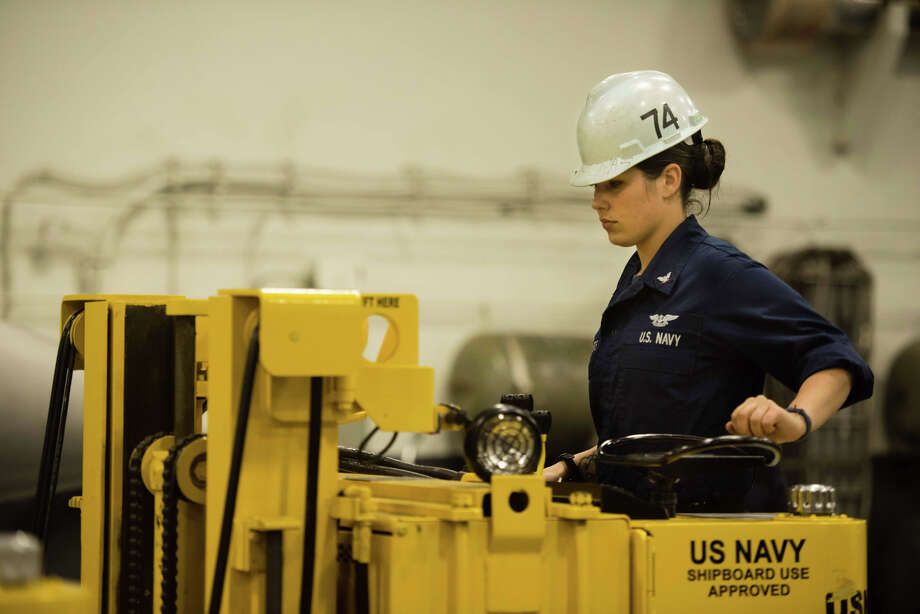 Mass Communication Specialist Seaman Kenneth Rodriguez Santiago / Navy Navy Aviation Ordnanceman 3rd Class Brittany Myers of Ephratah, Fulton County, drives an electrically enclosed fork lift in the hangar bay of the aircraft carrier USS John C. Stennis (CVN 74) in the Pacific.
