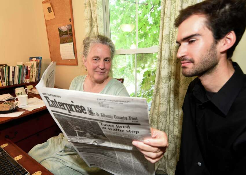 Co-publishers Melissa Hale-Spencer, left, and Marcello Iaia look over the first edition of the Altamont Enterprise that they produced as the new owners of the newspaper Monday morning, July 20, 2015. (Skip Dickstein/Times Union)
