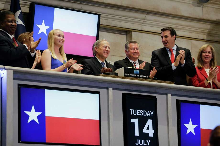 During a job-poaching trip to New York, Texas Gov. Greg Abbott, center, attends the opening bell ceremony at the New York Stock Exchange on July 14. Photo: Mark Lennihan, STF / AP