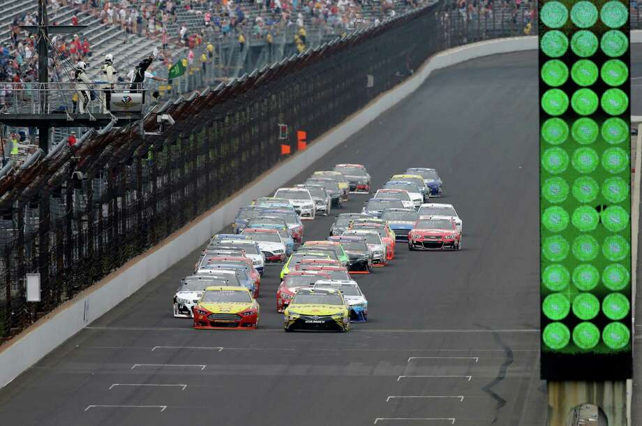 Sprint Cup Series drivers Carl Edwards (19) and Joey Logano (22) lead the field on the start of the NASCAR Brickyard 400 auto race at Indianapolis Motor Speedway in Indianapolis, Sunday, July 26, 2015.  (AP Photo/Darron Cummings) ORG XMIT: NAA103 Photo: Darron Cummings / AP