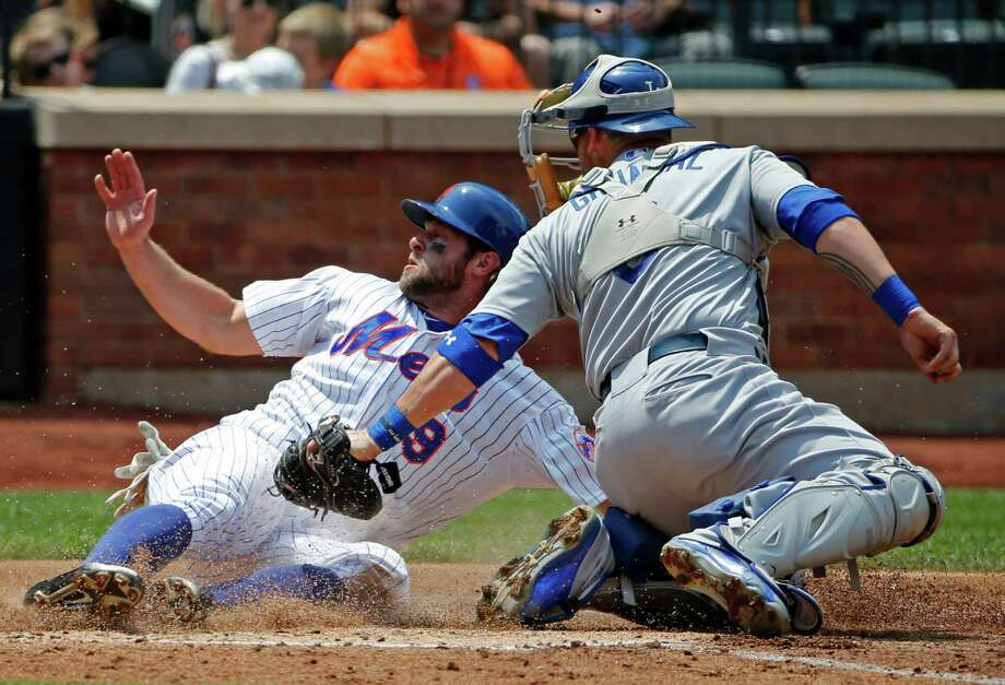 Los Angeles Dodgers catcher Yasmani Grandal, right, looks back for the call as New York Mets' Kirk Nieuwenhuis (9) scores on Jacob deGrom's third-inning RBI-single in a baseball game in New York, Sunday, July 26, 2015. (AP Photo/Kathy Willens) ORG XMIT: NYM105 Photo: Kathy Willens / AP