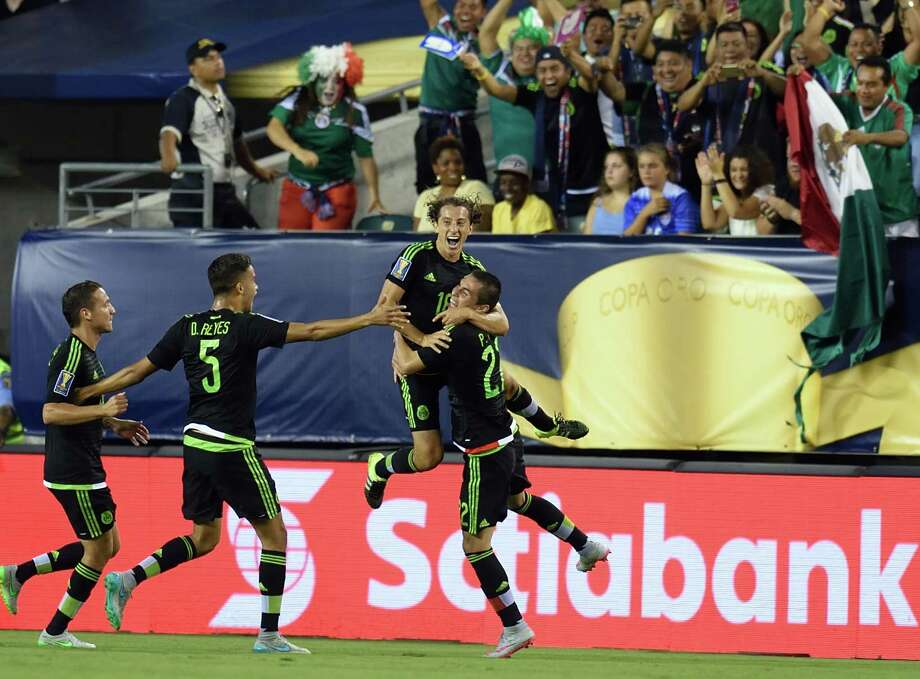 A goal in the 31st minute by Andres Guardado, top, gets the party started for Mexico. Photo: DON EMMERT, Staff / AFP