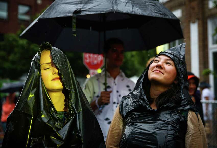 Fans try to stay dry during day three of Capitol Hill Block Party. The three day festival brings music and tens of thousands of fans to the center of Seattle's Capitol Hill neighborhood. Photographed on Sunday, July 26, 2015.