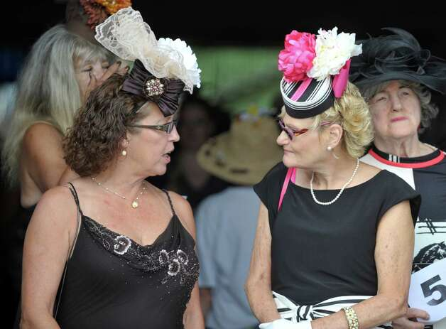 Friends, Jodi Brown, left, and Rose Poole, both from Amsterdam, talk before the start of the Fashionably Saratoga category during the 24th annual Hat Contest, presented by Hat Sational by DEI at the Saratoga Race Course on Sunday, July 26, 2015, in Saratoga Springs, N.Y.  (Paul Buckowski / Times Union) Photo: PAUL BUCKOWSKI / 00032762A