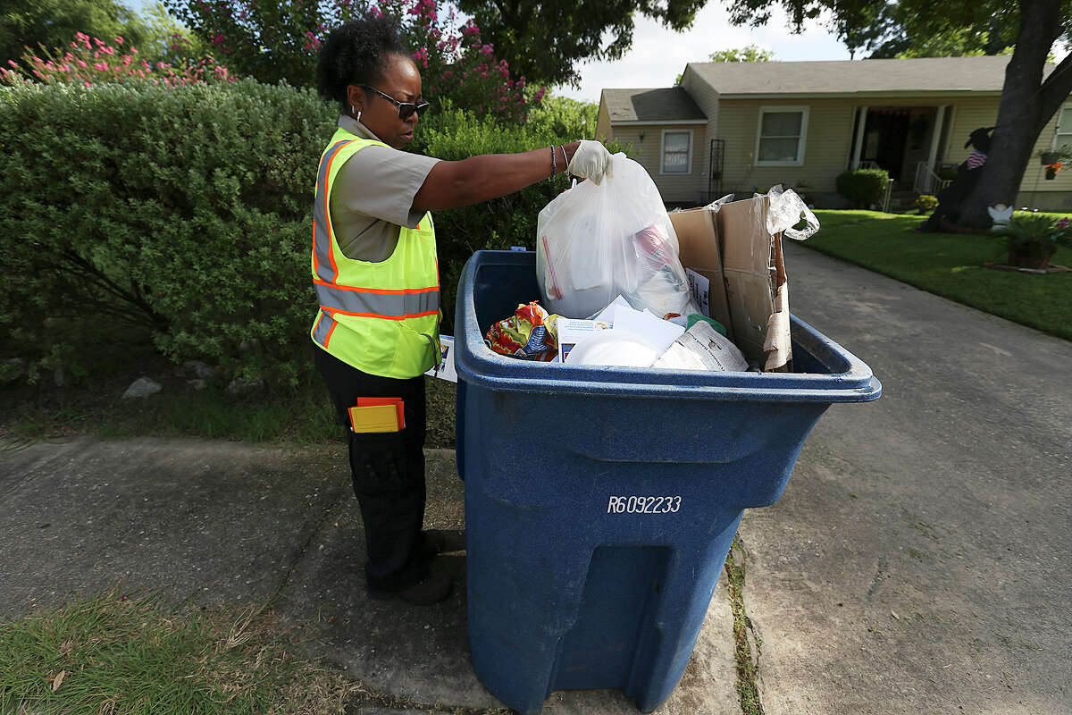 San Antonio Solid Waste Department route inspector Asia Jones-Carr finds household trash in a recycling can along her route on West Mandalay Drive and West Thorain Boulevard near Blanco Road, Monday, July 20, 2015. Household garbage and air conditioning filters are among items not allowed in the can and in this case, the homeowner was allowed to remove the items. In other cases, services can be refused.