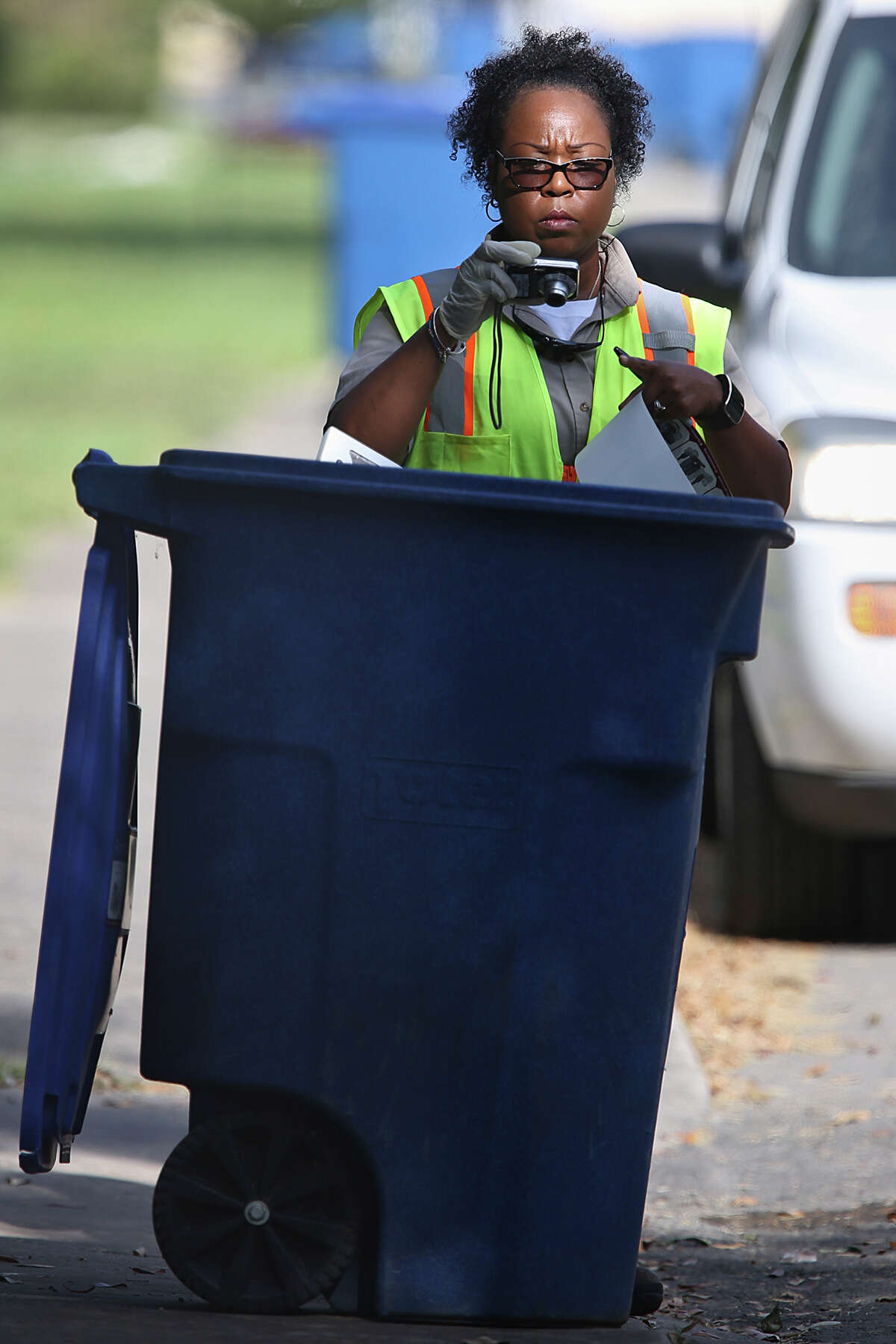 San Antonio Solid Waste Department route inspector Asia Jones-Carr photographs a recycling can with unauthorized items while on her route on West Mandalay Drive and West Thorain Boulevard near Blanco Road, Monday, July 20, 2015. Household garbage and air conditioning filters are among items not allowed in the can and in this case services was refused.