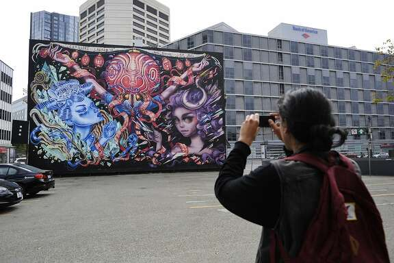 Jesus Beltran of San Francisco stops to take a phone picture of a large mural on Market Street at Van Ness Avenue in San Francisco, CA Sunday, July 26 2015.