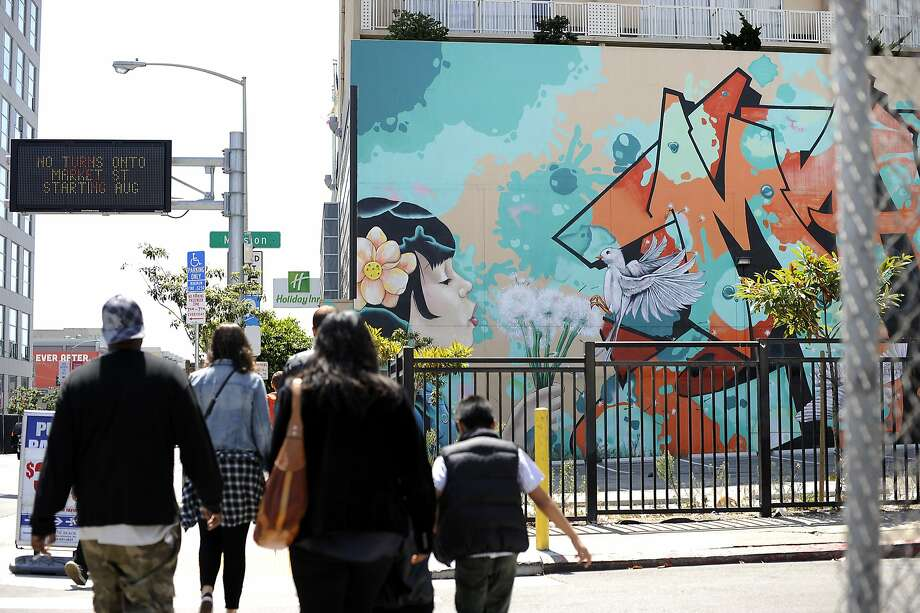 Pedestrians walk past a large mural that covers the wall in a parking lot of the Holiday Inn on 8th St. between Market and Mission streets in San Francisco, CA Sunday, July 26 2015. Photo: Michael Short, Special To The Chronicle