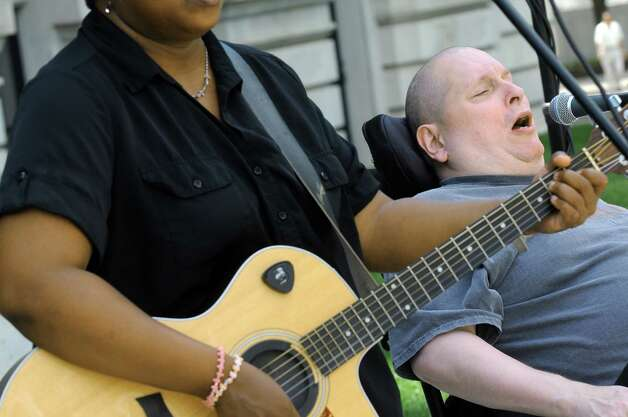 Scott Stuart, right, takes lead on a song with the band Flame, a group of talented musicians who happen to have disabilities, as they perform during a celebration of the 25th Anniversary of the signing of the landmark Americans with Disabilities Act (ADA) at the West Park of the Capitol on Friday July 24, 2015 in Albany, N.Y. (Michael P. Farrell/Times Union) Photo: Michael P. Farrell / 00032753A