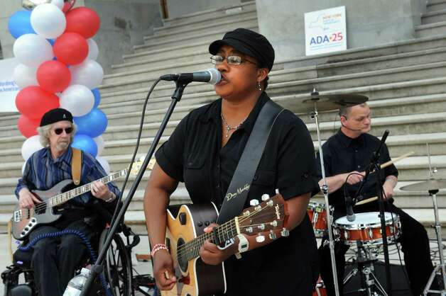 Lead singer Michelle King, center, fronts the band Flame, a group of talented musicians who happen to have disabilities, as they perform during a celebration of the 25th Anniversary of the signing of the landmark Americans with Disabilities Act (ADA) at the West Park of the Capitol on Friday July 24, 2015 in Albany, N.Y. (Michael P. Farrell/Times Union) Photo: Michael P. Farrell / 00032753A