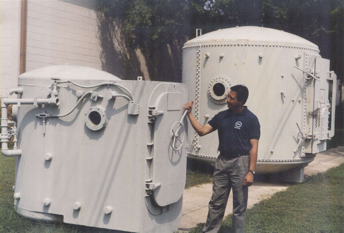 Brooks' Hangar 9 curator Fernando Cortez stands next to Airman Farrell's chamber and near a much-larger Mineola Chamber used by Wiley Post, an aviation pioneer who was a friend of humorist Will Rogers.