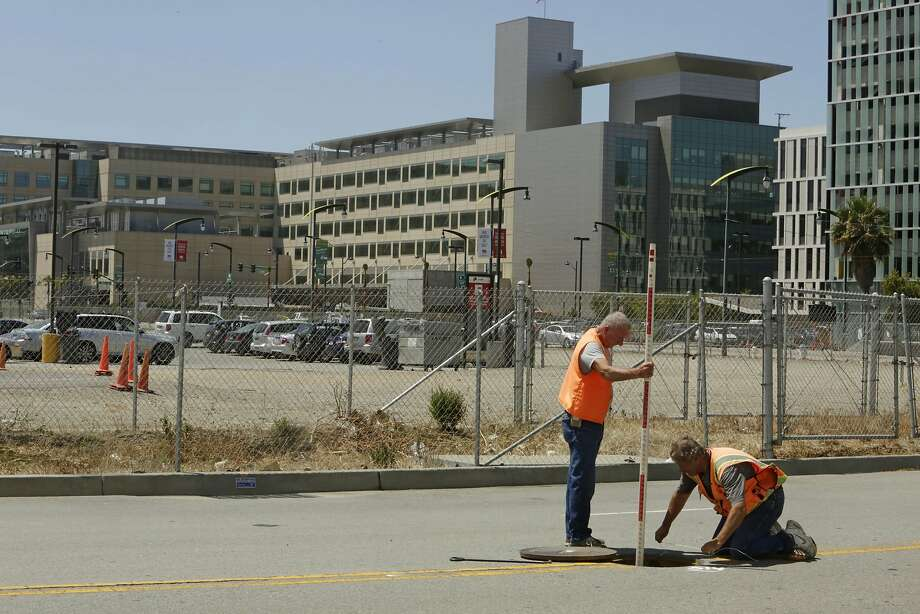 Land surveyors John Seace (l to r) and Frank Montemurro, both of John Seace Land Surveying, work on South Street next to the site of the proposed Golden Gate Warriors arena on Monday, July 27, 2015 in San Francisco, Calif.  In the background is seen the UCSF Medical Center at Mission Bay. Photo: Lea Suzuki, The Chronicle