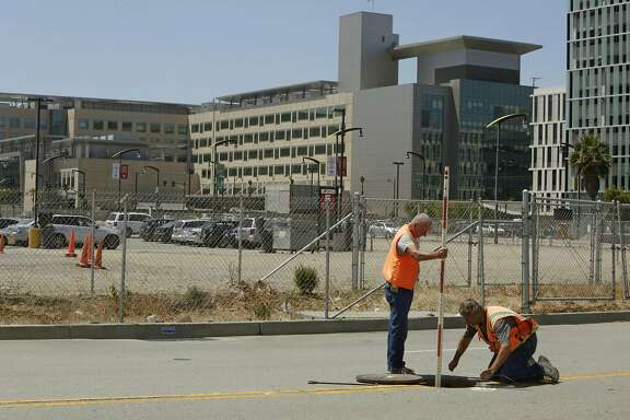 Land surveyors John Seace (l to r) and Frank Montemurro, both of John Seace Land Surveying, work on South Street next to the site of the proposed Golden Gate Warriors arena on Monday, July 27, 2015 in San Francisco, Calif.  In the background is seen the UCSF Medical Center at Mission Bay.