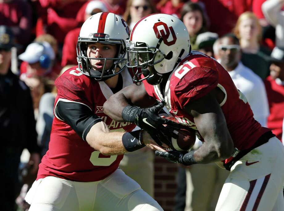 Oklahoma quarterback Trevor Knight (9) hands off to Keith Ford (21) in the second quarter of an NCAA college football game against Baylor in Norman, Okla., Saturday, Nov. 8, 2014. Photo: Sue Ogrocki /Associated Press / AP