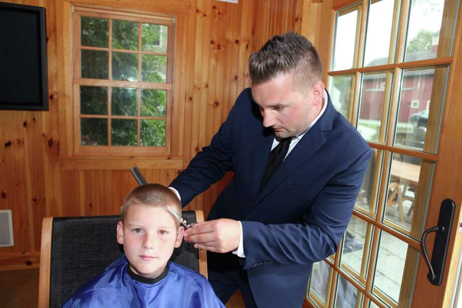 Christian Iannucci gives 10-year-old Hunter Stolze, of Oxford, a trim in his family's living room. Photo: Contributed / Contributed Photo / Stamford Advocate  contributed