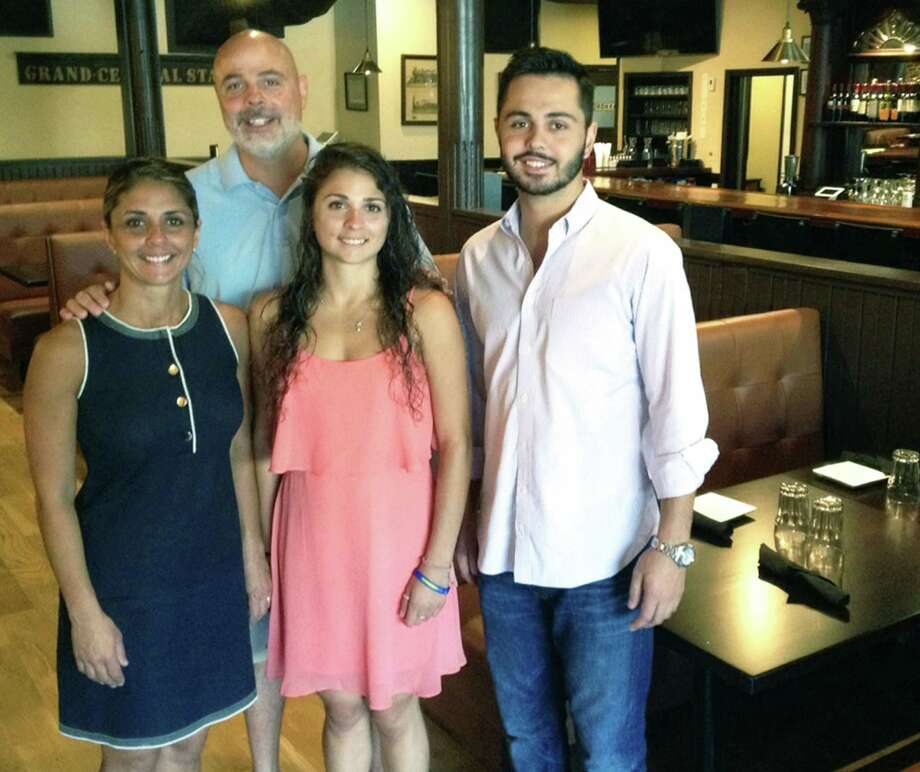 The Iron Rail is very much a family-run restaurant along Railroad Street in downtown New Milford. Mary Ann and Chuck Kapetanopoulos share the experience with their daughter, Georgia, and their son, Yiannis, who serves as manager. Photo: Norm Cummings / Norm Cummings / The News-Times