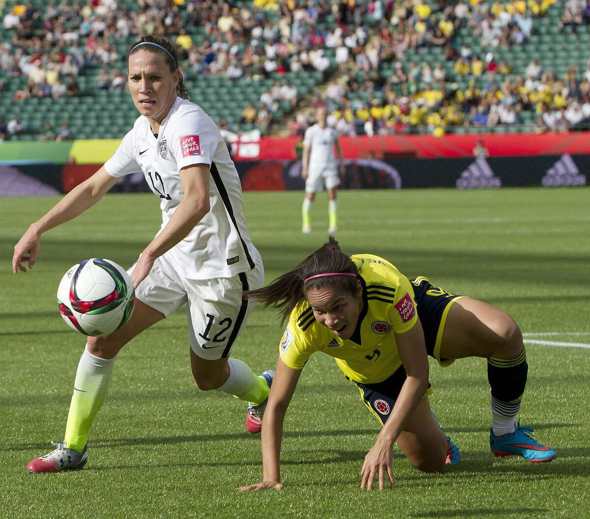 FILE - In this June 22, 2015, file photo, United States' Lauren Holiday (12) and Colombia's Orianica Velasquez, right, battle for the ball during the first half of a second round game at the FIFA Women's World Cup in Edmonton, Alberta, Canada. U.S. soccer formally announced Monday, July 27, 2015, that midfielders Shannon Boxx and Holiday will retire from the U.S. national team following a victory tour to celebrate the Women's World Cup title. (Jason Franson/The Canadian Press via AP, File) MANDATORY CREDIT