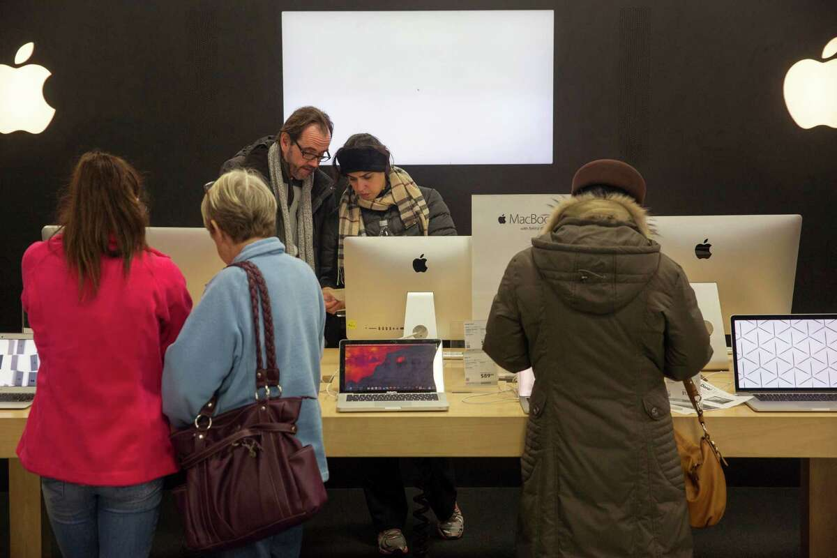 INDIANAPOLIS, IN - NOVEMBER 27: Shoppers examine Apple products while looking for Black Friday deals Thanksgiving evening at a Best Buy on November 27, 2014 in Indianapolis, Indiana. Many retailers open the evening before the famous shopping day. (Photo by Aaron P. Bernstein/Getty Images)
