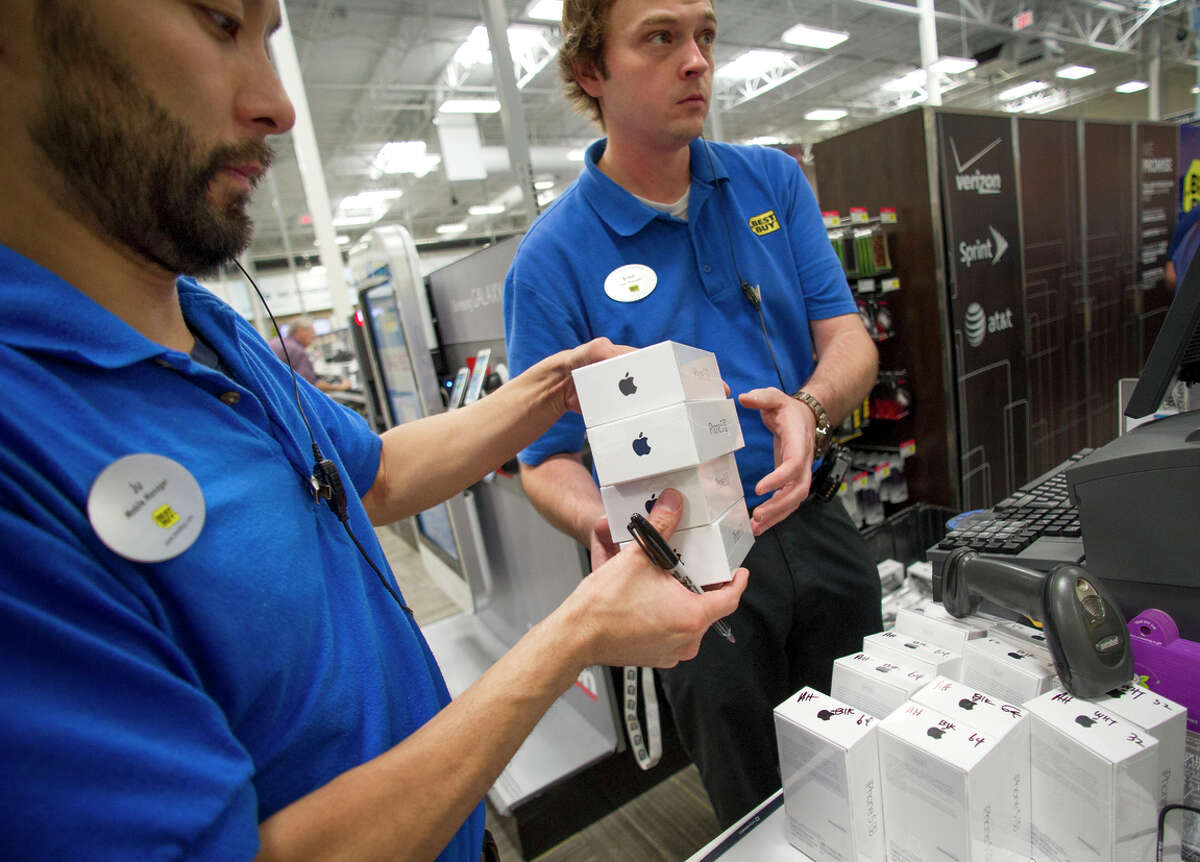Managers Ju Lee (left) and Brad Deep ready iPhones for sale at a Best Buy in Atlanta in 2013. Best Buy sells more Apple products than Apple.