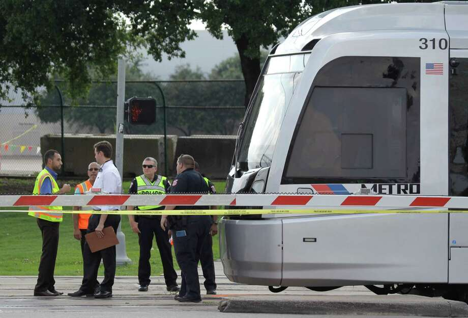 Emergency personnel work at the scene where a Metro train hit and killed a pedestrian on June 2. Photo: Melissa Phillip, Staff / © 2015  Houston Chronicle