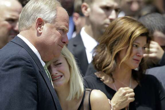 Family members mourn after the funeral of Mayci Breaux, one of the two people killed in a Louisiana movie theater last week. Her sister Ali Breaux, center, cries after the funeral Monday at the Church of the Assumption in Franklin, La., while accompanied by their mother, Dondie LeBlanc Breaux, right.