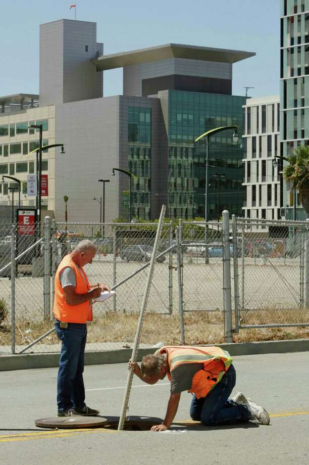 Land surveyors John Seace (left) and Frank Montemurro work on South Street next to the proposed site for a new Golden State Warriors arena. The UCSF Medical Center can be seen in the background. Photo: Lea Suzuki / Lea Suzuki / The Chronicle / ONLINE_YES