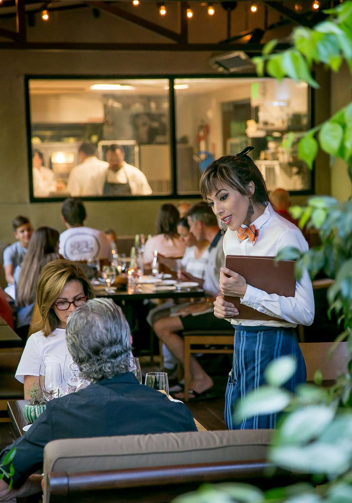 Server Alma Candelas talks with diners at Harvest Table in St. Helena, Calif., on July 26th, 2015.