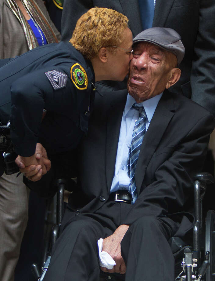 Sgt. G. Captain kisses retired officer Edward A. Thomas on the cheek before Monday's ceremony. Photo: Cody Duty, Staff / © 2015 Houston Chronicle