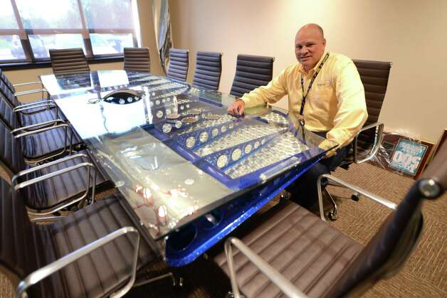 IntegraOptics CEO David Prescott sits a meeting room desk which was made from the wing of DC-3 airplane Monday, July 27, 2015, at IntegraOptics in Colonie, N.Y. (Will Waldron/Times Union) Photo: WILL WALDRON / 00032783A