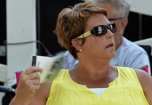Robin Hahn of Cobleskill uses a program to keep cool Monday afternoon at the Saratoga Race Course in July 27, 2015 in Saratoga Springs, N.Y.    (Skip Dickstein/Times Union) Photo: SKIP DICKSTEIN
