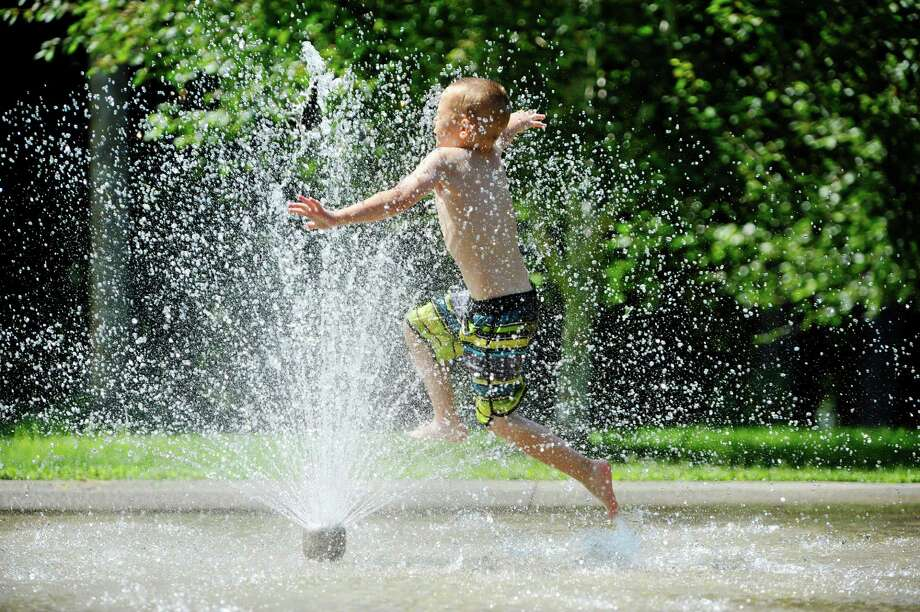 Avery Murray, 6, of Watervliet jumps through the spray pool to stay cool at Prospect Park on Monday, July 27, 2015, in Troy, N.Y.  (Paul Buckowski / Times Union) Photo: PAUL BUCKOWSKI / 00032775A