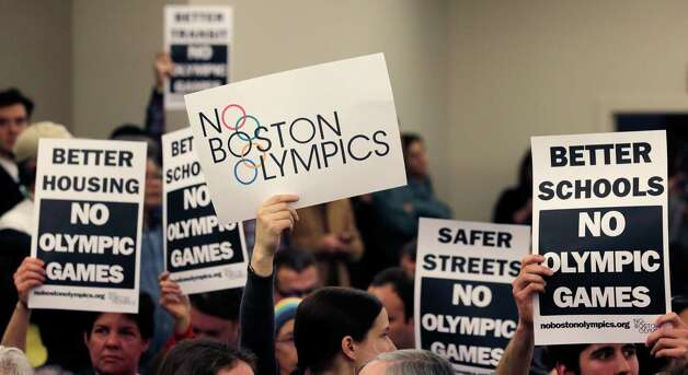 "FILE - In this Feb. 5, 2015, file photo, people hold up placards against the Olympic Games coming to Boston, during the first public forum regarding the city's 2024 Olympic bid, in Boston. Boston's mayor delivered a harsh blow to the city's effort to host the 2024 Olympics on Monday, July 27, 2015,  when he declared he wouldn't sign any document ""that puts one dollar of taxpayer money on the line for one penny of overruns on the Olympics.""  That document is the host city contract that most in the Olympics consider crucial to any city's success.  (AP Photo/Charles Krupa, File) ORG XMIT: NY156 Photo: Charles Krupa / AP"