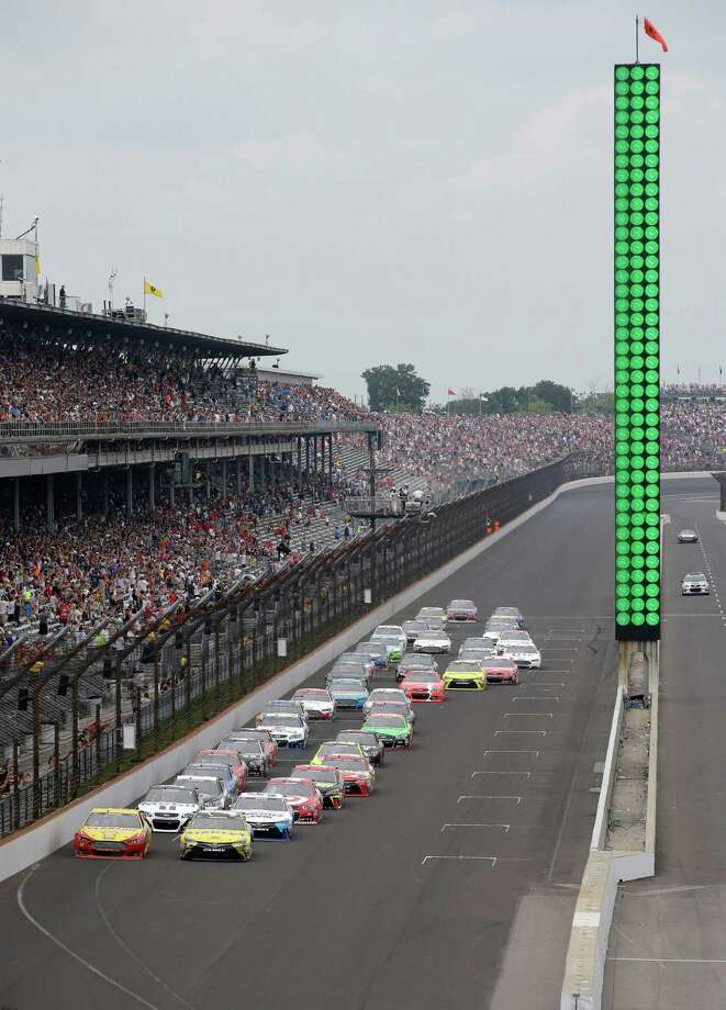 Sprint Cup Series drivers Carl Edwards (19) and Joey Logano (22) lead the field on the start of the NASCAR Brickyard 400 auto race at Indianapolis Motor Speedway in Indianapolis, Sunday, July 26, 2015.  (AP Photo/Darron Cummings) ORG XMIT: NAA104 Photo: Darron Cummings / AP