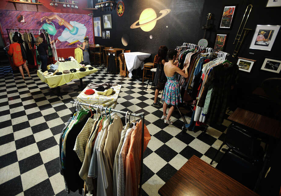 "Shoppers browse the wares at the Logon Cafe on Monday night. The Logon Cafe hosted a Swanky Vintage Night shopping event Monday night for Jade Oliver as she prepares to make the move to New York City. Oliver said there were about 300 items for sale, representing around a third of her stock, and that everything else would make the trip to her shop in New York. The event also included a showing of ""On the Town,"" starring Gene Kelly and Frank Sinatra. Photo taken Monday 7/27/15 Jake Daniels/The Enterprise Photo: Jake Daniels / ©2015 The Beaumont Enterprise/Jake Daniels"