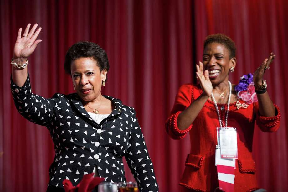 Attorney General Loretta Lynch, left, waves as she stands with Carla Harris at Monday's Delta Sigma Theta Sorority convention lunch. Photo: Brett Coomer, Staff / © 2015 Houston Chronicle