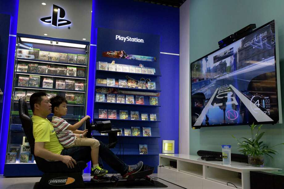 A sales person helps a child try out a video game at a shop in Beijing, Monday, July 27, 2015. China is lifting its ban on sales of video game consoles to promote the industry and a new manufacturing zone in Shanghai. (AP Photo/Ng Han Guan) Photo: Ng Han Guan, STF / AP