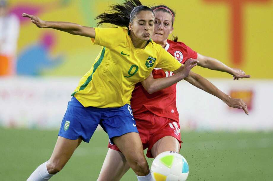 Canada's Chelsea Stewart, back, and Brazil's Andressa Alves battle for the ball during the Pan Am Games women's soccer match in Hamilton, Ontario, Sunday, July 19, 2015. (Peter Power/The Canadian Press via AP) Photo: Peter Power, SUB / The Canadian Press