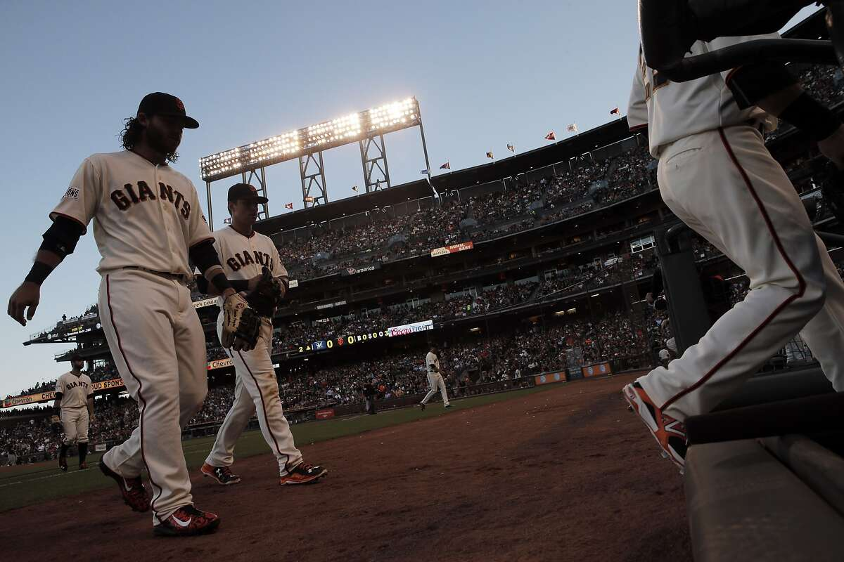 Brandon Crawford (35) and Joe Panik (12) return to the dugout at the end of the first inning as the Giants played the Milwaukee Brewers at AT&T Park in San Francisco, Calif., on Monday, July 27, 2015. The Giants