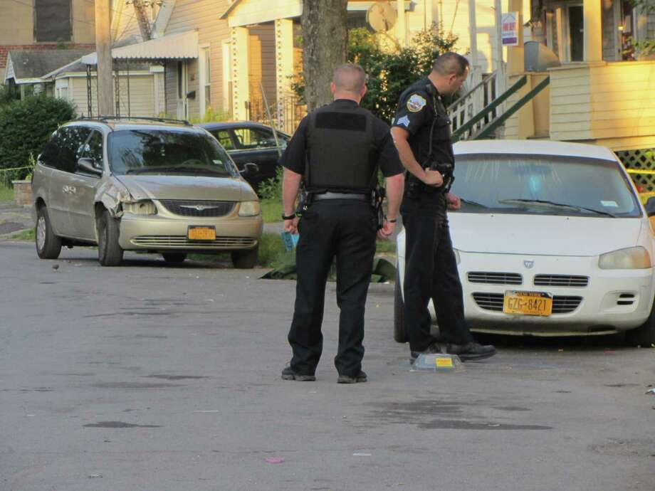 Officers survey the scene at first light Tuesday where a Schenectady teen was shot dead on Schenectady Street near Van Voast Street. Multiple shell casings were marked with yellow numbers in a vacant lot across the way and near a while sedan where the 18-year-old was found and rushed to the hospital. He was pronounced dead on arrival, police said. (Bob Gardinier / Times Union)