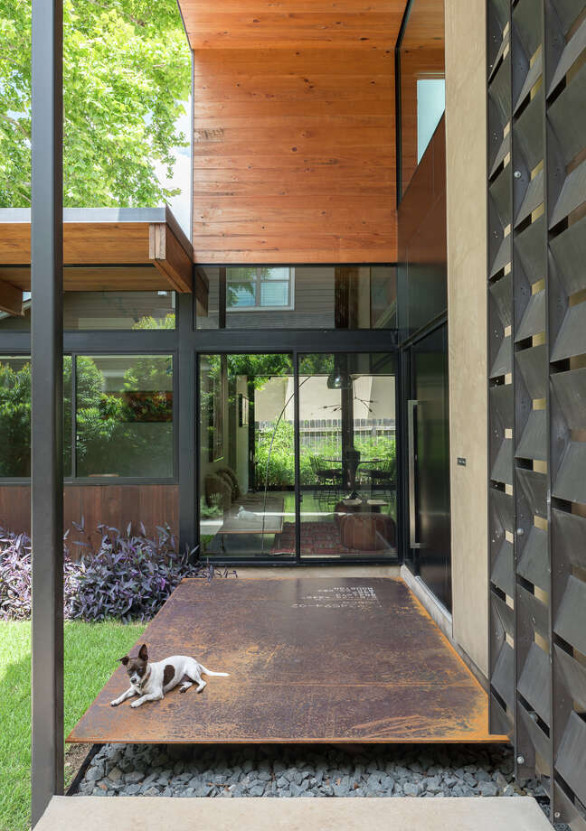 At the Alamo Heights home of Tobin and Courtney Smith, glass walls allow in abundant natural light and a seamless connection to the outdoors. Reclaimed steel provides a step-up entry to the home. Photo: Courtesy Mark Menjivar / / Mark Menjivar