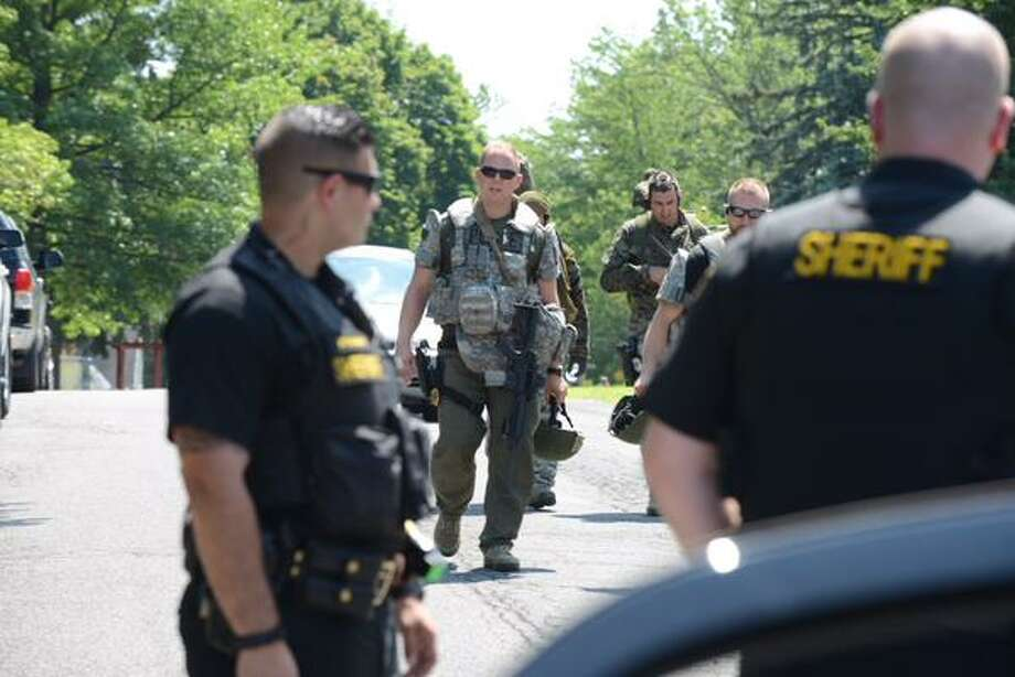 Colonie police leave a home on Hoffman Drive Tuesday afternoon. Police descended on the home amid a report of gun fire. (Will Waldron / Times Union)