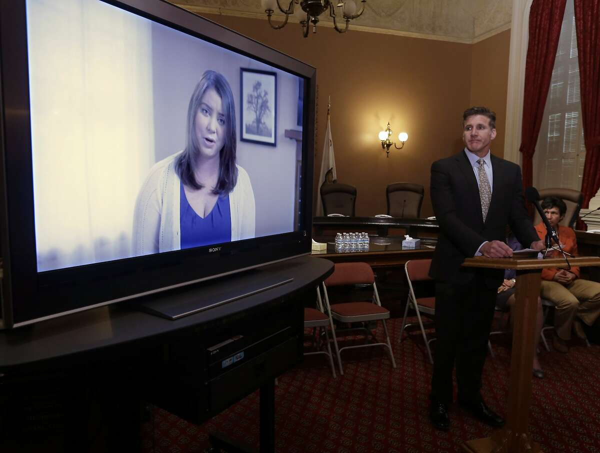 FILE - In this March 25, 2015 file photo, Dan Diaz, the husband of Brittany Maynard, watches a video of his wife, recorded 19 days before her assisted suicide death, where she says that no one should have to leave their home to legally end her life, during a news conference at the Capitol in Sacramento, Calif.