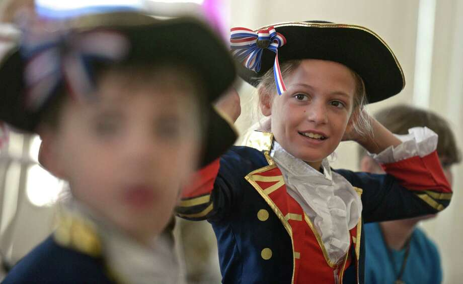 "Tishy Cacciapaglia, 11, of Ridgefield, gets dressed as a Minute Man for a re-enactment of the ""Battle of Ridgefield""  at the Keeler Tavern, in Ridgefield. Summer campers at the museum re-enact the ""Battle of Ridgefield"", from the American Revolution, after spending the week as ""history detectives""  and learning about the people in that period of our history. On Friday, July 24, 2015, in Ridgefield, Conn. Photo: H John Voorhees III / Hearst Connecticut Media / The News-Times"