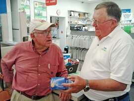 ADVANCE FOR SUNDAY, JULY 26, 2015 In this June 25 2015 photograph, Philadelphia, Miss., resident, Barney Shepherd, left, gets help from part-time Fred's pharmacist, Donny Kitchens. Shepherd, a Medicare recipient, has seen the price of his diabetic testing strips spike in recent weeks. (Monica Land/The Clarion-Ledger, via AP)