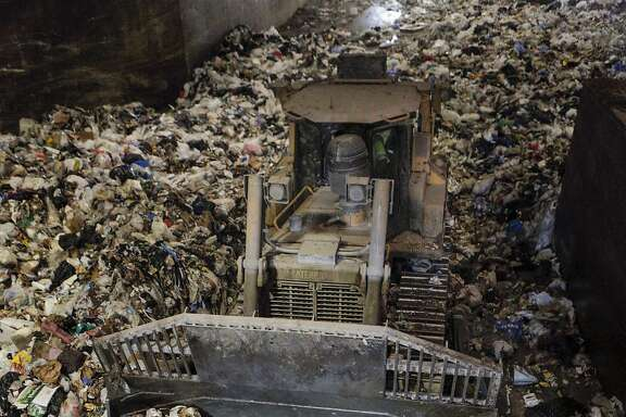 A bulldozer top-loads a long haul transfer truck with garbage from a holding area above at the Recology San Francisco Transfer Station in San Francisco, CA, on Friday, July 24, 2015. The trucks take the refuse to Altamont Landfill in Livermore, CA.