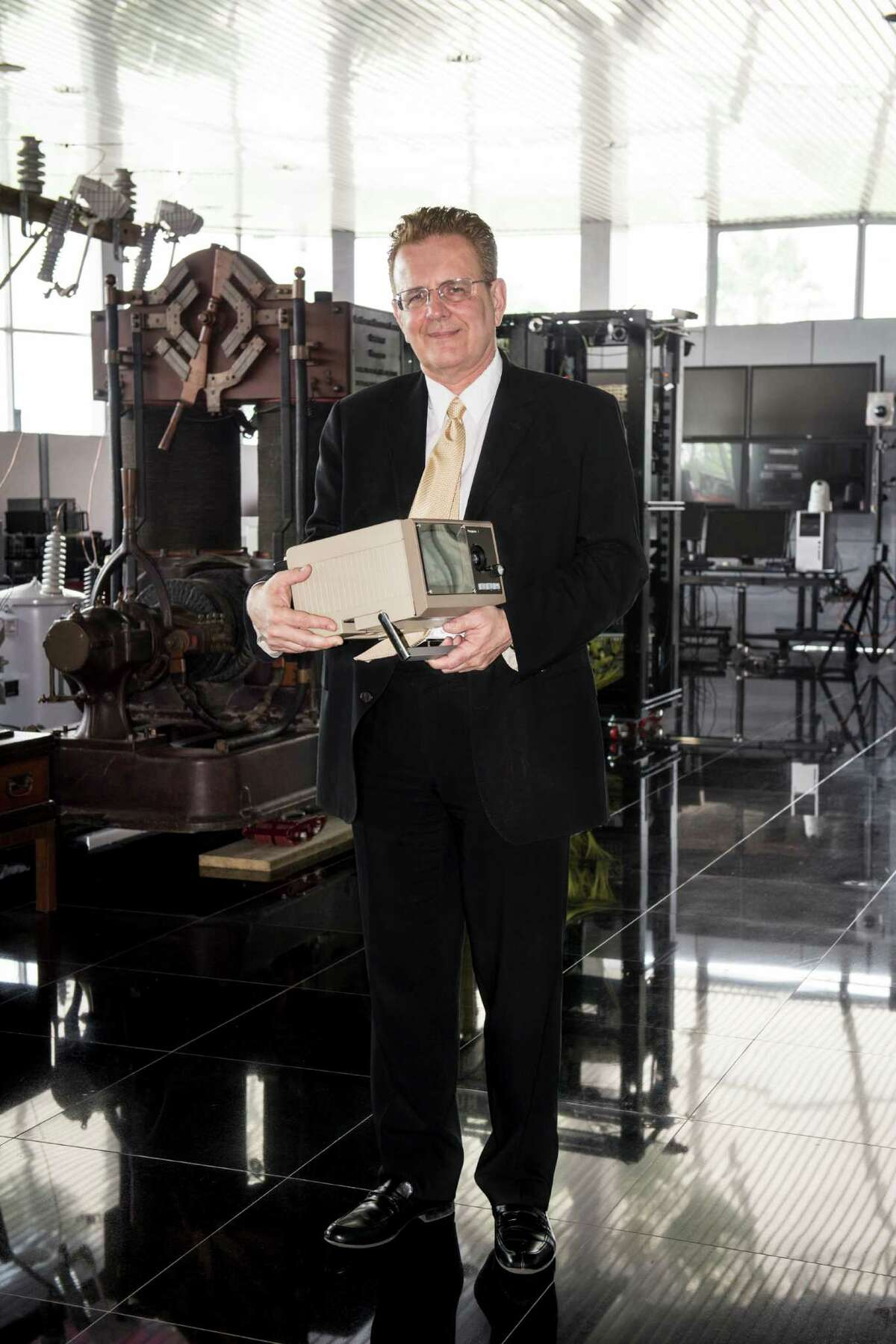 San Antonio tech pioneer David Monroe holds an early version of an image transmission system, the invention on which he based his company, Photophone Ltd., in 1983.
