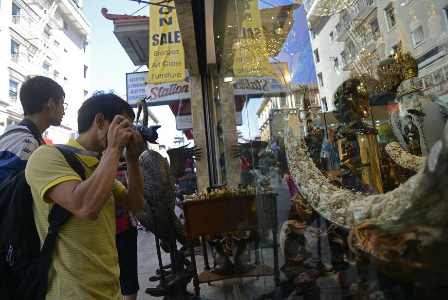 Lang da Yin takes a photo of a mammoth ivory tusk in the window of Rare Art & Antiques store in San Francisco China Town in California, on Tuesday, July 28, 2015. President Obama announced a new measure last Saturday that would eliminate the ivory trade in the United States. Photo: Brandon Chew, The Chronicle
