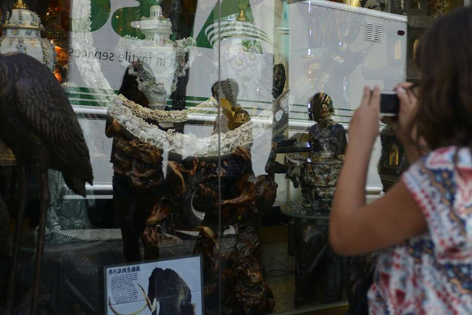 People pass by a mammoth ivory tusk in the window of Rare Art & Antiques store in San Francisco China Town in California, on Tuesday, July 28, 2015. Photo: Brandon Chew, The Chronicle